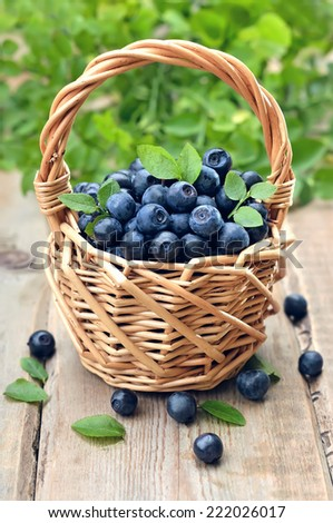 Fresh ripe blueberries in wicker basket on wooden table - stock photo