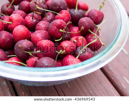 Fresh ripe cherries in glass bowl on red wood background - stock photo