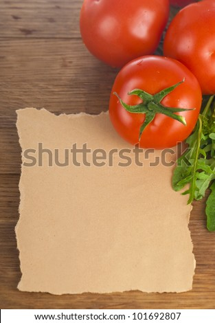 Fresh, ripe cherry tomatoes on an old chopping board. Basil leaves in the background - stock photo