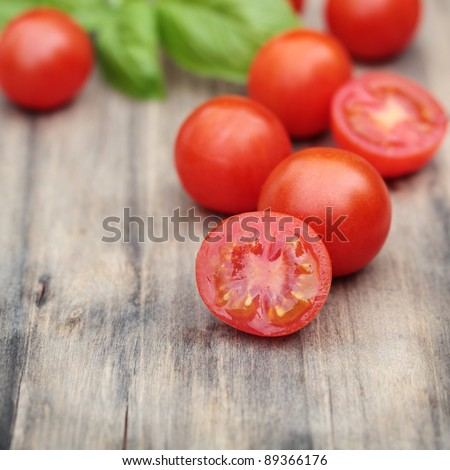 Fresh, ripe cherry tomatoes on an old chopping board. Basil leaves in the background. - stock photo