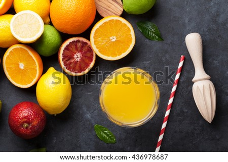 Fresh ripe citruses and juice. Lemons, limes and oranges on dark stone background. Top view - stock photo
