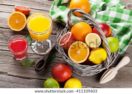 Fresh ripe citruses and juice. Lemons, limes and oranges on wooden background - stock photo