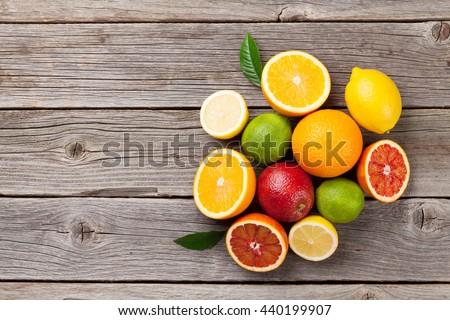 Fresh ripe citruses. Lemons, limes and oranges on wooden table. Top view with copy space - stock photo