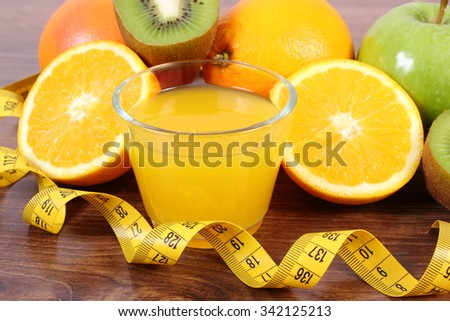 Fresh ripe fruits, glass of juice and tape measure on wooden surface plank, grapefruit orange kiwi apple, healthy lifestyles nutrition and strengthening immunity - stock photo
