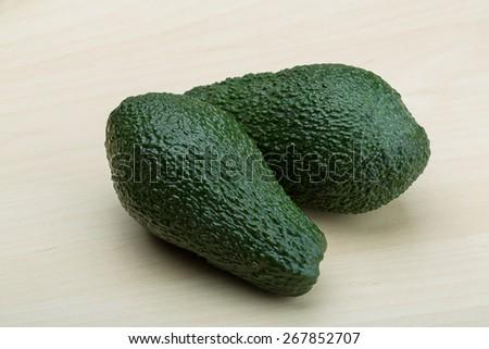 Fresh ripe green avocado on the wood background - stock photo
