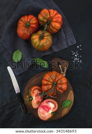 Fresh ripe heirloom tomatoes and basil leaves on rustic wooden board over black stone background., top view - stock photo