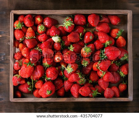 Fresh ripe juice strawberries in wood box over dark wooden background. Top view - stock photo