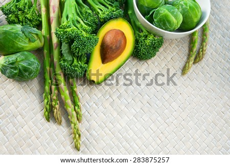 Fresh ripe juicy and delicious vegetables brocolli, brussels sprouts, bunch of asparagus, avocado cut in halves, herbs and spices on a wickered mat on a table ready to be cooked. Top view, copy space - stock photo