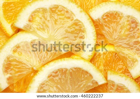 Fresh ripe juicy orange and lemon slices close-up as background. Top view point. - stock photo