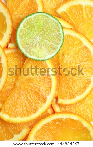 Fresh ripe juicy orange and lime slices close-up as background. Top view point. - stock photo