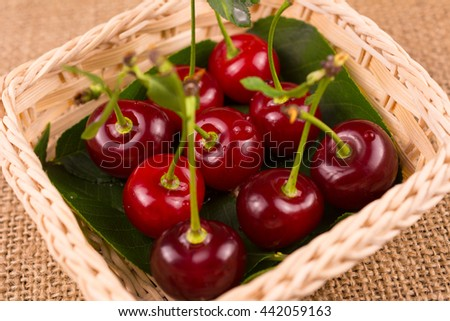 Fresh, ripe, juicy sour cherries in small wicker basket - stock photo