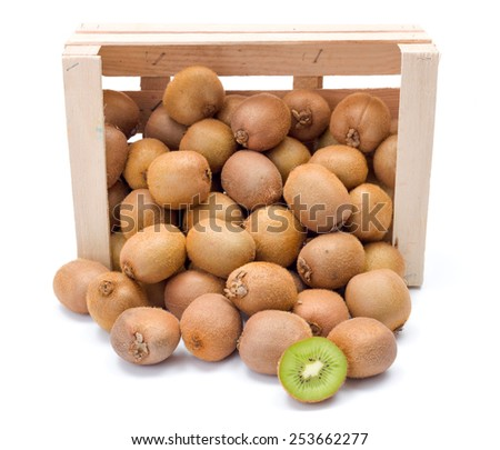 Fresh ripe kiwifruits spilling out of wooden crate. Chinese gooseberry - stock photo