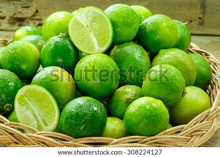 Fresh ripe limes in basket on wooden table - stock photo