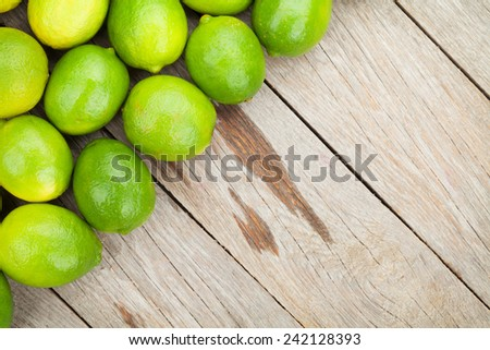 Fresh ripe limes on wooden table with copy space - stock photo