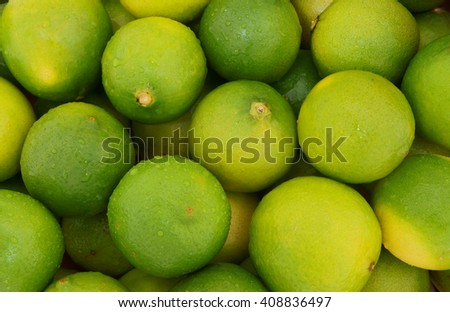 Fresh ripe limes with drops of water as background - stock photo