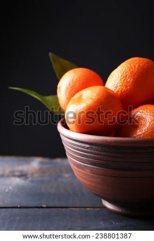 Fresh ripe mandarins in bowl, on wooden table, on dark  background - stock photo