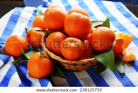 Fresh ripe mandarins on wicker basket, on napkin, on wooden background - stock photo