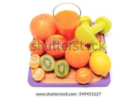 Fresh ripe natural fruits, dumbbells for using in fitness and glass of juice, concept for slimming, healthy nutrition and strengthening immunity - stock photo