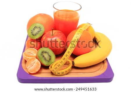 Fresh ripe natural fruits, glass of juice and tape measure on cutting board, concept for slimming, healthy nutrition and strengthening immunity - stock photo