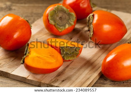 Fresh ripe persimmon on a wooden table. Selective focus. - stock photo