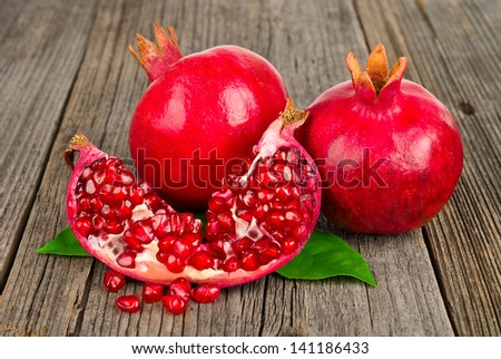 Fresh ripe pomegranates with leaves on an old wooden board - stock photo