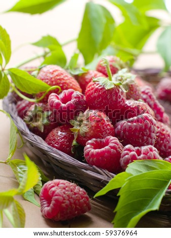 Fresh, ripe raspberries and strawberries in little wooden berry baskets. - stock photo