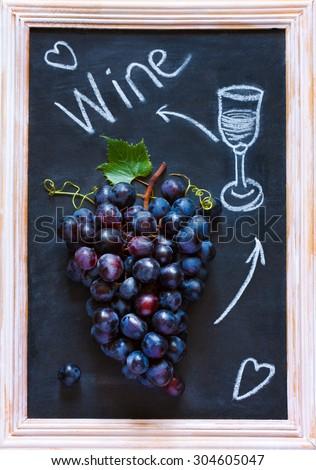 Fresh ripe red grape cluster on old chalk board. Invitation card. - stock photo