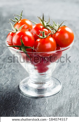 Fresh ripe red juicy cherry tomatoes with stalks served in a conical glass container as crudites to dip in a savory sauce - stock photo