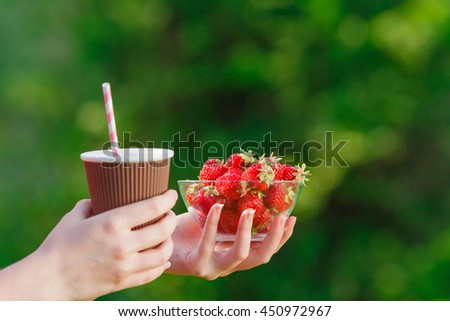 fresh ripe red juicy strawberries and coffee in hands of young woman  on nature background. Healthy eco sweet food rich in vitamins.  - stock photo