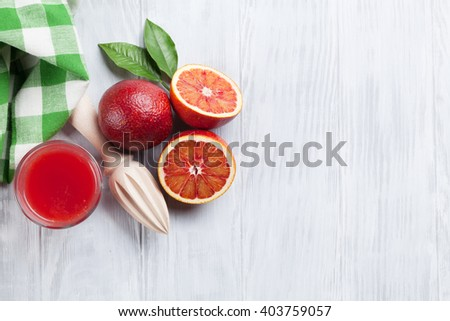 Fresh ripe red oranges and juice on wooden table. Top view with copy space - stock photo