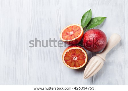 Fresh ripe red oranges and juicer on wooden table. Top view with copy space - stock photo