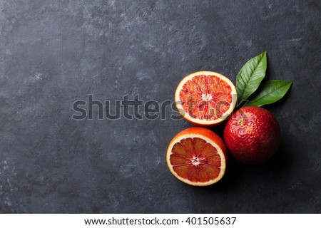 Fresh ripe red oranges on dark stone background. Top view with copy space - stock photo