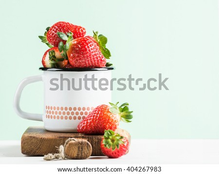 Fresh ripe red strawberries in country style enamel mug on rustic wooden board, pastel light lilac background, selective focus, copy space - stock photo