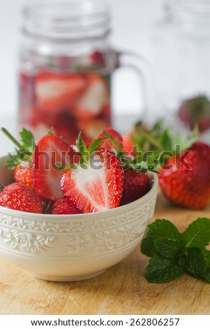 Fresh ripe red strawberries in white bowl on wooden - stock photo
