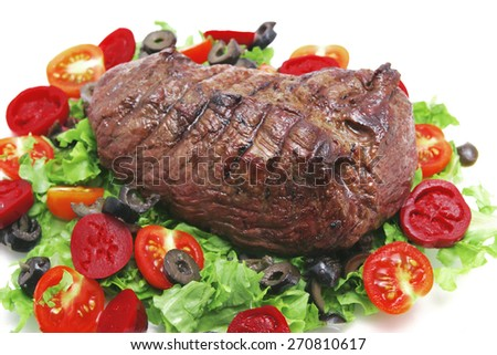fresh ripe roasted big chunk of beef meat on green salad with tomatoes isolated on white - stock photo
