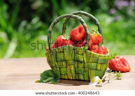 Fresh ripe strawberries in a rustic basket  on wooden table in the garden - stock photo
