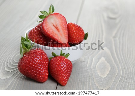 fresh ripe strawberries in a simple white bowl, on wood table - stock photo