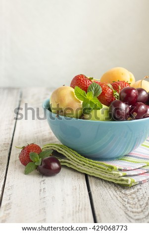 Fresh Ripe Sweet Fruits in a blue cup on the Wooden Table . Fresh Organic Food. Fresh Berries. Summer berries. Place for text, copy space - stock photo