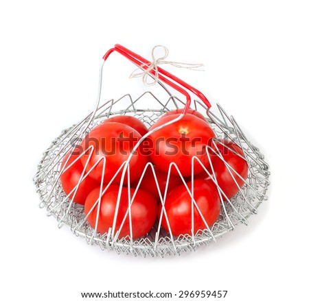 Fresh ripe tomatoes in a metal mesh folding basket bag on a white background with a place for the text. - stock photo