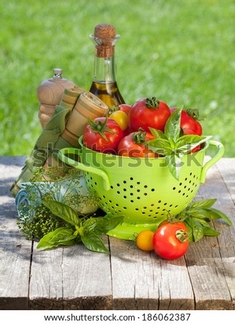 Fresh ripe tomatoes, olive oil bottle, pepper shaker and basil on wooden table - stock photo