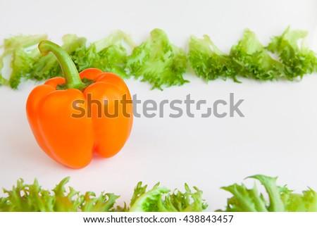 Fresh ripe vegetables - sweet  orange pepper and leaves of frillis. Bell peppers. - stock photo