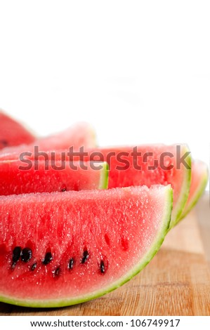 fresh ripe watermelon sliced on a  wood table over white background - stock photo