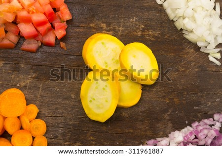 fresh ripe zucchini, carrots, tomatoes and onion chopped on a wooden board and shot from above - stock photo