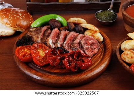 fresh roast bbq beef meat ribeye steak on wooden plate served with tomato juice in wooden cup, boiled broccoli, baked tomatoes and potatoes, with white bun, red wine glass on light walnut wooden table - stock photo