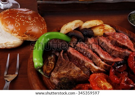 fresh roast bbq beef meat ribeye steak on wooden plate served with tomato juice iwooden cup, boiled broccoli, baked tomatoes and potatoes, with white bun, red wine glass light walnut wooden table - stock photo