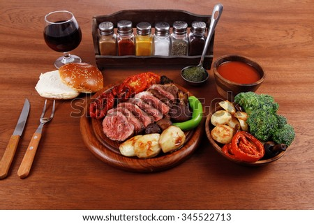 fresh roast bbq beef meat ribeye steak on wooden plate served with tomato juice wooden cup, boiled broccoli, baked tomatoes and potatoes, with white bun, and red wine glass light walnut wooden table - stock photo