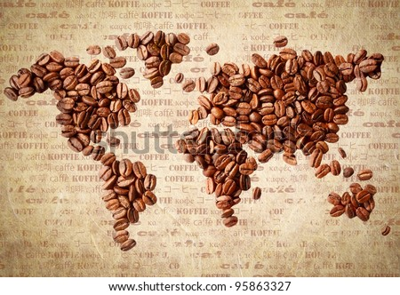 Fresh roasted coffee beans arranged in the shape of a world map on aged vintage paper with the word coffee in multiple languages. - stock photo