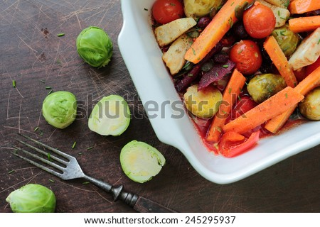 Fresh roasted vegetables in the oven-pan on wooden table - stock photo