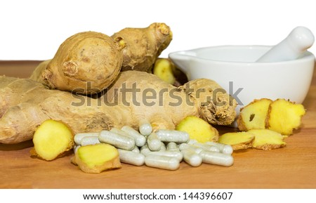 Fresh root ginger with whole and sliced rhizomes alongside a white ceramic pestle and mortar and a pile of capsules conceptual of plant extracts and supplements - stock photo