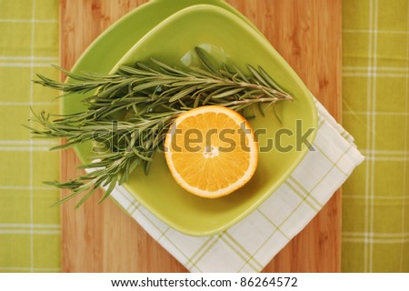 Fresh rosemary and orange at green plate with checked serviette - stock photo